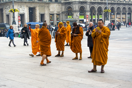 Buddhist monks with phones in the square near the Cathedral of Milan.