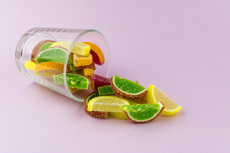 Multi-colored marmalade in the form of citrus slices in a transparent glass, which lies on a pink background Stockfoto