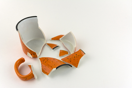 Broken orange mug on white background. Numerous pieces of the Cup. Imagens
