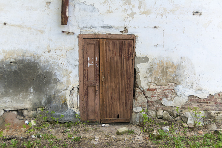 The wall of an old house with a door. Fallen off plaster, brick wall. Imagens