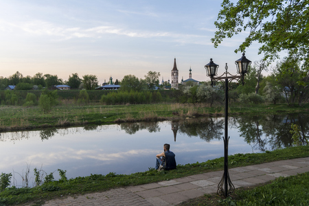 Suzdal, Russia, 10 may 2019. Typical Russian landscape. Church above the river in the city of Suzdal. A young man sitting on the Bank of the river. Editorial