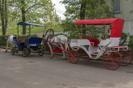 Walking carriages drawn by horses in the old streets of Suzdal. Russia