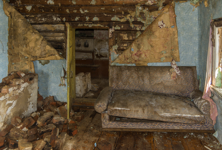 Old abandoned farmhouse. The sofa in the room. Ruin and dirt.