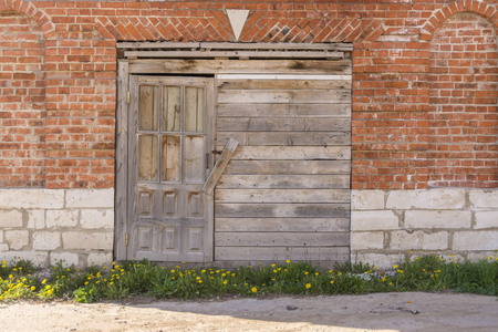 Boarded up wooden door to an old warehouse in a brick wall.