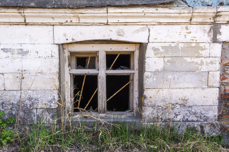 Old basement window with broken glass and metal bars