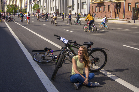 Moscow. Russia. 19 may 2019. Moscow Cycling festival Velofest 2019. Numerous cyclists ride along a wide street. Girl cyclist resting on the road