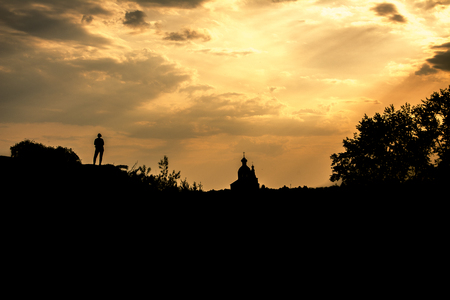 Silhouette of a girl and the Orthodox Church against the sky. Suzdal, Russia.