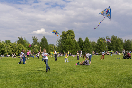 Moscow. Russia. 26 may 2019. People relax on a large lawn in the Park Tsaritsyno. Launch into the sky colorful kites. Editorial