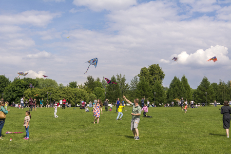 Moscow. Russia. 26 may 2019. People relax on a large lawn in the Park Tsaritsyno. Launch into the sky colorful kites Imagens - 124584872