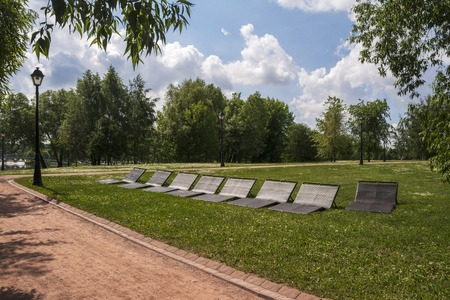 Sunbeds for relaxing in the Park. Green alleys and paths.