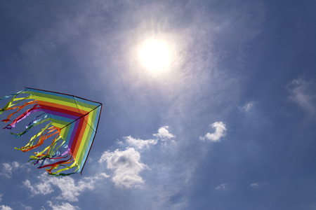 Colorful kite flying in blue sky background sky. Bright sun.