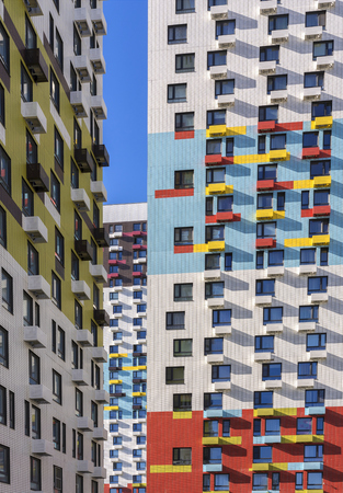 View of the facade of a multi-storey residential building. Colorful elements in the design of the building.