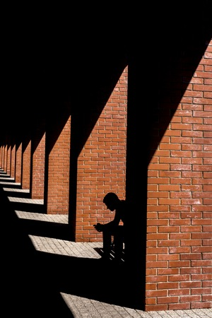 The silhouette of a man sitting on a bench in the loft.