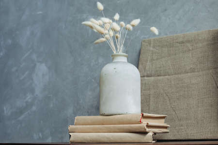 dry flowers in an old vase on the background of a linen painting . space for text.