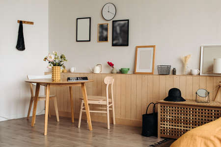 Wooden dining table in a bright home interior. On the table are peonies in a designer yellow vase . Paintings, photo frames avoska in the background.Lifestyle flowers on the kitchen table. Home.