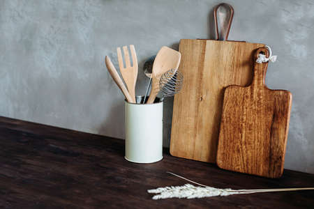 Kitchen appliances.Metal and wooden. fork, spoon, and spatula on a wooden table top, against a gray textured wall. . Kitchen still life for cooking as a background for the design. A copy of the space.