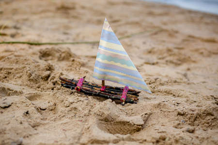 One toy boat on sandy beach A toy sailing ship in the rive Фото со стока