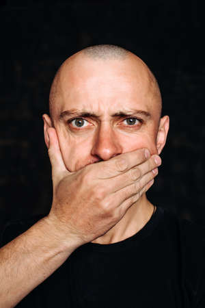 the bald man covers his mouth with his hand .Fear is the fear of speaking. 版權商用圖片
