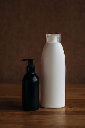 White and black plastic bottle with hand sanitizer on a beige background. Body cosmetics .