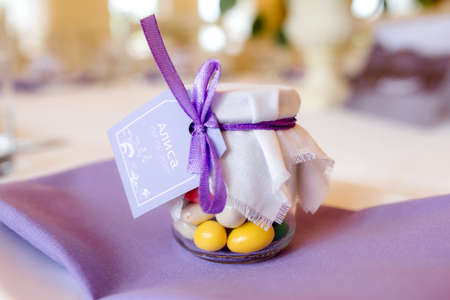 Gift for guests. Wedding bonbonniere-sweets in a jar covered with a white cloth with a bow . on a purple napkin. Archivio Fotografico