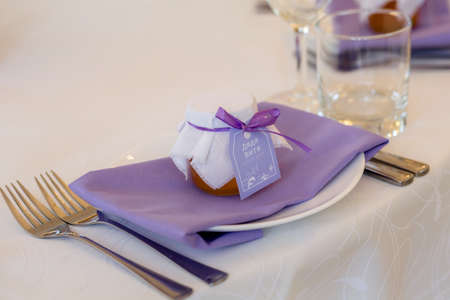 A gift for guests is a jar of honey on a plate. Wedding bonbonniere-honey in a jar covered with a white cloth with a bow. on a purple napkin. wedding table setting. decor in the purple palette Archivio Fotografico