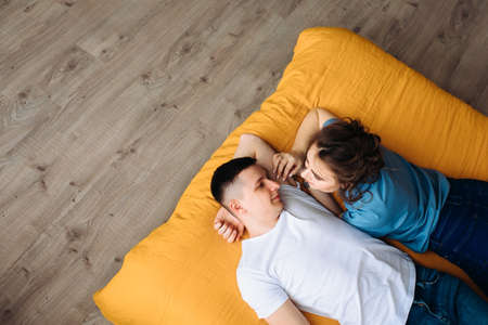 newlyweds in love in a cozy home environment. Beautiful young couple in the bedroom lies on the bed. Resting at home. Enjoying spending time together. A happy family. Smiling, dreaming, talking. Foto de archivo