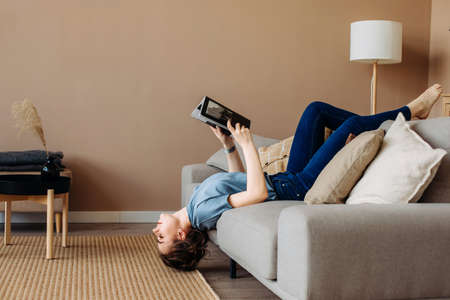 Girl reading a book lying on the couch upside down in the living room at home, romantic mood. Calm stylish interior. The woman in blue casual clothes. Lifestyle