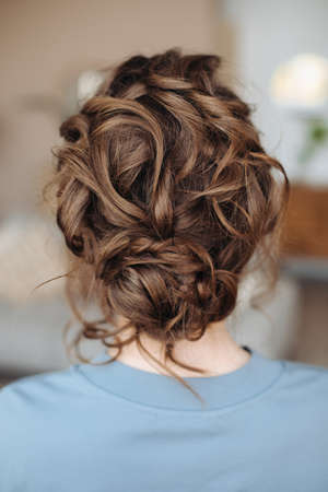 Complex hairstyle on the head of a brown-haired woman, rear view close-up. Fashionable professional women's hairstyle. Wedding hairstyle. Evening look. Blue dress