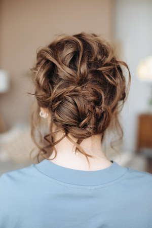Complex hairstyle on the head of a brown-haired woman, rear view close-up. Fashionable professional women's hairstyle. Wedding hairstyle. Evening look. Blue dress.every day hairstyle