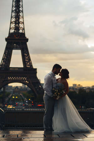 silhouette of the bride and groom in the evening against the background of the Eiffel tower. The moment before the kiss. Stock Photo
