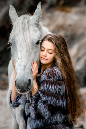 The friendship of woman and animal. cool weather, a teenage girl with long curly hair in a fur coat.