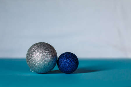 tree decoration blue and silver colors of different sizes are arranged in a row on a turquoise and whait background.