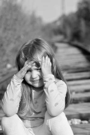 railtrack: Girl child sitting on abandoned railtrack Stock Photo