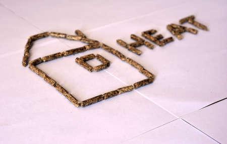 Beeld van de korrels van de korrelbrandstof op witte achtergrond in beeld van huis en brieven worden geïsoleerd die