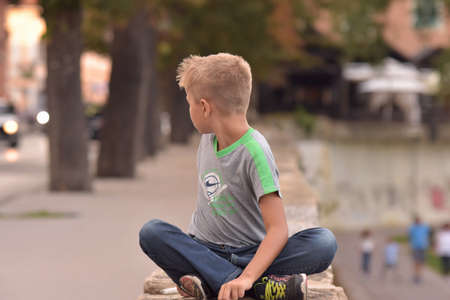 Image of young blond boy sitting crossed leg outdoor looking over his shoulder