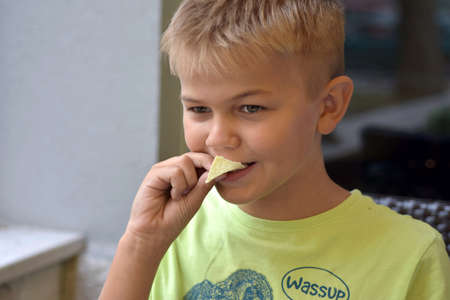 Portrait image of young blond boy taking bite of snack food