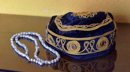 Islamic muslim prayer cap and beads necklace rosemary isolated on reflective background