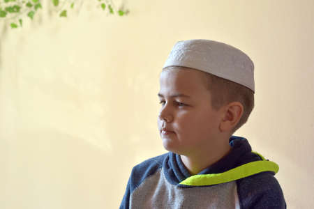 Portrait image of young muslim boy wearing traditional islamic prayer cap. place to put text in image