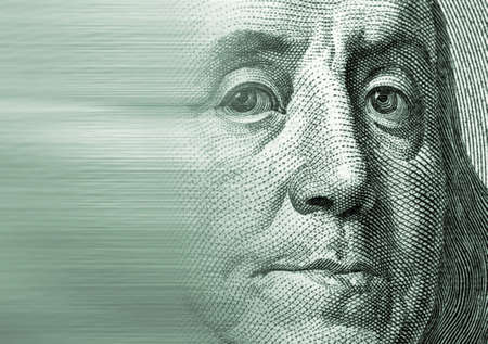 well build: Zoomed to a particular note of a hundred U.S. dollars representing the face of Franklin with motion effect