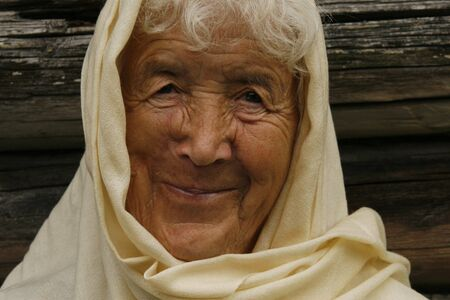 oldage: old woman wrapped in a beige scarf