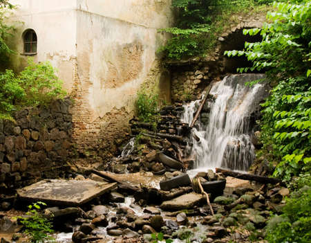 Small waterfall in the park in Vilnius near Old house photo