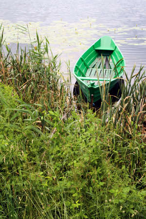 green boat: Small green boat on a calm lake Stock Photo