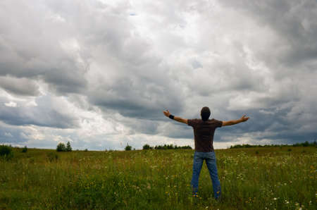 man praying: man standing on the field and raising his hands up to the clouds Stock Photo