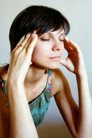 young woman with closed eyes massaging her head photo