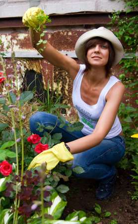 young female in gloves and hat working in the garden photo