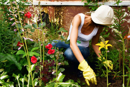 female in gloves and hat working in the garden