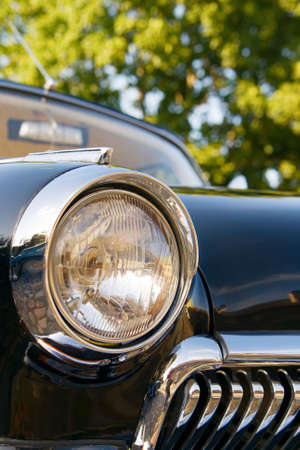 closeup headlight and grille of an old black classic car photo