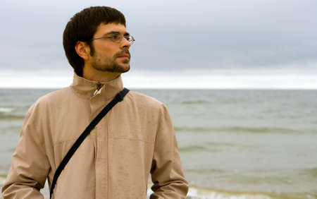portrait of a young beautiful man in glasses near the Baltic sea