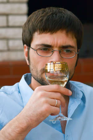 wine testing: portrait of a man testing and smelling white wine Stock Photo