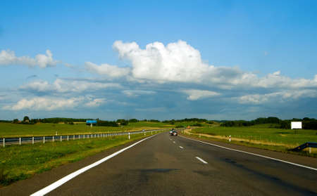 country highway with blue sky and clouds in Lithuania photo